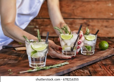A female bartender offers a cocktail of fresh lime and rosemary