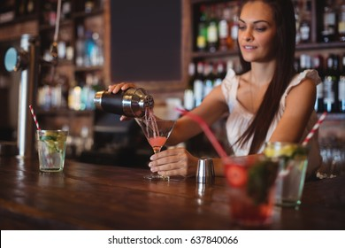 Female bartender pouring cocktail drink in the glass at bar counter