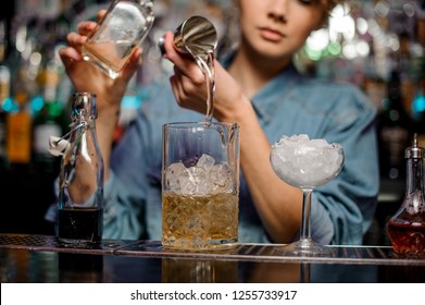 Female bartender pouring to the measuring cup with ice cubes an alcoholic drink from steel jigger on the bar counter on the blurred background