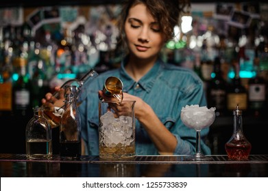 Female bartender pouring to the measuring glass cup with ice cubes an alcoholic drink from jigger on the bar counter on the blurred background