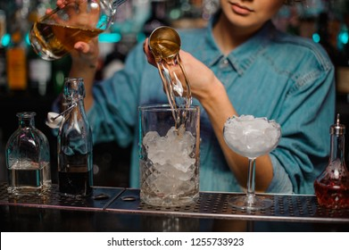Female bartender pouring to the measuring glass cup with ice cubes a yellow alcoholic drink from steel jigger on the bar counter on the blurred background