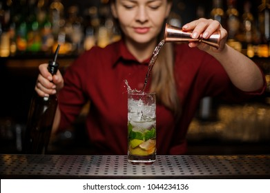 Female bartender pouring out a transparent drink from the measuring pile with splash for preparing a delicious fresh cocktail