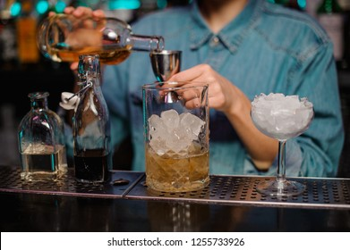 Female bartender pouring to the steel jigger an alcoholic drink on the bar counter in the foreground of measuring cup, glass with ice and bottles