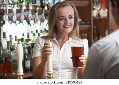 Female Bartender Serving Drink To Male Customer