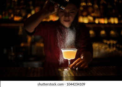 Female bartender serving a fresh delicious yellow cocktail and pouring a spice into it on the bar counter