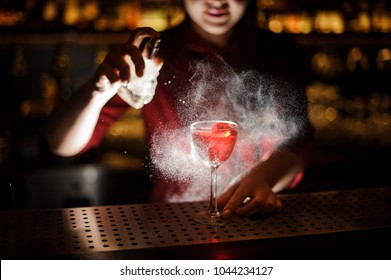 Female bartender spraying on the fresh delicious cocktail for serving it on the steel bar counter