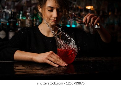 Female bartender throwing to red cocktail glass standing on the bar counter an ice cube with splash on the blurred background