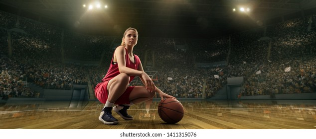 Female basketball player with ball on big professional arena