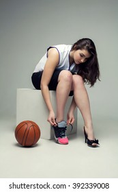 Female basketball player changing her running shoes