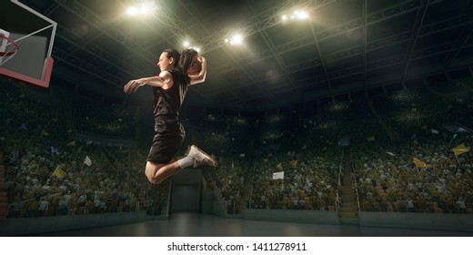Female basketball player makes slam dunk. Basketball player on big professional arena during the game