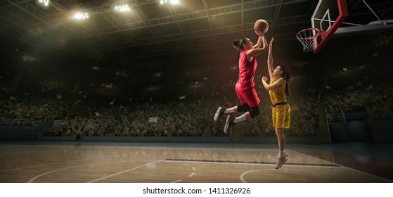 Female basketball players fight for the ball. Basketball player makes slam dunk on big professional arena during the game