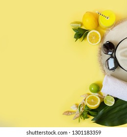 Female beach accessory. Straw sunhat, sunglasses, and water on punchy yellow. Top view and space for text. Summer travel concept.