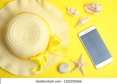 Female beach hat, smartphone and seashells on a yellow background.