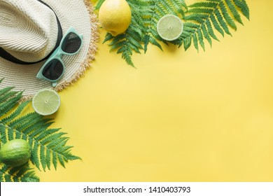 Female beach straw sunhat, sunglasses, citrics on punchy yellow. Top view and space for text. Summer travel concept.