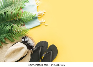 Female beach straw sunhat, sunglasses, flip flops on punchy yellow. Top view and space for text. Summer travel concept.