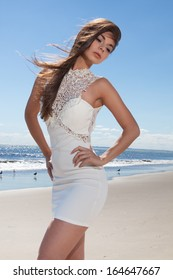 female at the beach with a white dress on