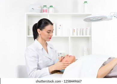Female beautician doctor with patient in wellness center. Professional cosmetologist make procedure to beautiful girl in cosmetology cabinet or beauty parlor.
