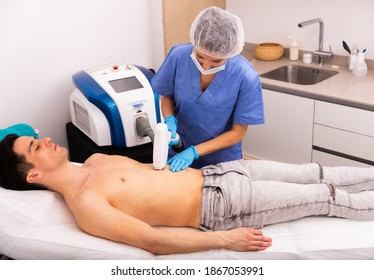 Female beautician doing hair removal cosmetology procedure to young man, male skincare concept
