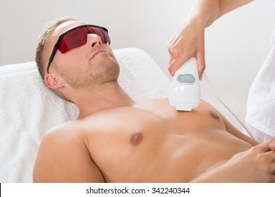 Female Beautician Giving Laser Epilation On Man's Chest