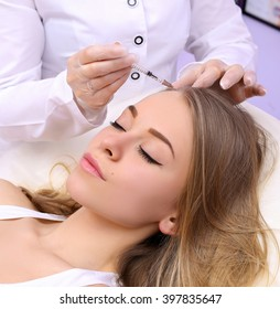 Female beautician makes injection of vitamins and minerals in the scalp. The concept of hair loss.