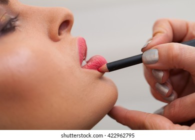 Female beautician using lip brush and applying color on young woman's lips.