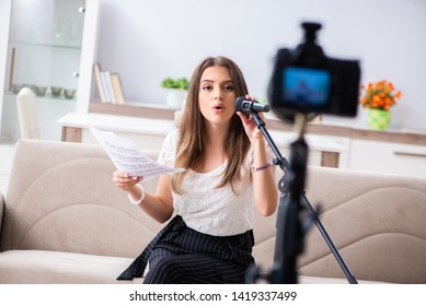 Female beautiful blogger singing at home