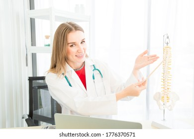 A female beautiful doctor is wearing a doctor uniform currently recommending treatment using a vertebral model look into the camera in the examination room in the hospital or clinic.