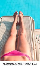 Female beautiful legs on sunbed near swimming pool