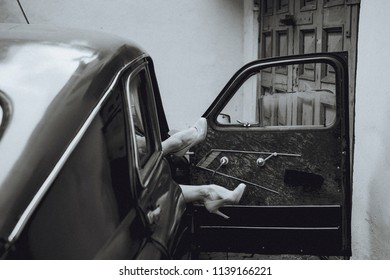 Female beautiful legs in shoes stick out of the car. Black and white photography