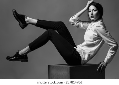 Female beauty concept. Portrait of fashionable young girl in classic clothes posing over gray background. Perfect hair & skin. Vogue style. Studio shot