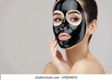 Female Beauty Face Skin Masking. Closeup Beautiful Sexy Young Woman With Natural Makeup And Cosmetic Black Peel Mask On Facial Skin. Attractive Girl Applying Peeling Product On Face. High Resolution