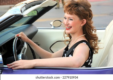 Female beauty fashion model sitting in her classic convertible car.