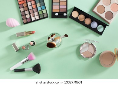 Female beauty items on mint colour background. Make up products, foundation, mascara, brushes