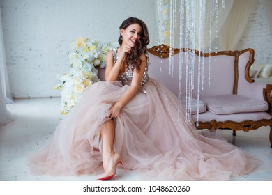 Female beauty. Luxury woman portrait with perfect hair and make-up. Attractive young lady in elegant dress posing in sensual way on sofa