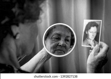 Female beauty, senior caucasian woman looking at the mirror and at the her young photo. Memories