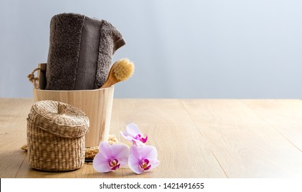 female beauty still life concept with towel, face dry brush, orchids with wooden bucket for zero waste shower and indulging bath, copy space