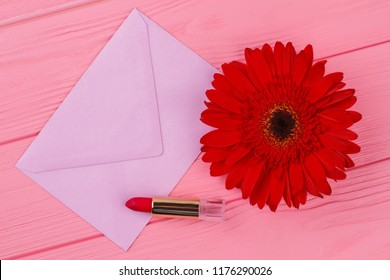 Female belongings and envelope. Post mail, red lipstic and red daisy flower. Pink wooden table background.