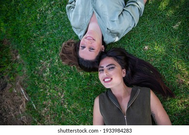 Female best friends lying on a grass meadow, head to head smiling. Friendship and freedom concept.