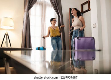 Female best friends on vacation as travel partners, excited about arriving at hotel room in destination. Lesbian couple with luggage smiling and impressed about bed and breakfast booking. LGBT tourism