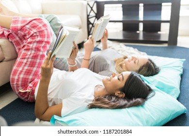 Female best friends in pajamas lying together and reading novels at home