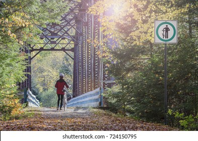 female bicyclist obeying bicycle trail rules when crossing bridge on corridor aerobique trail in province of quebec, canada