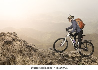 Female biker riding on bicycle in mountains on sunset