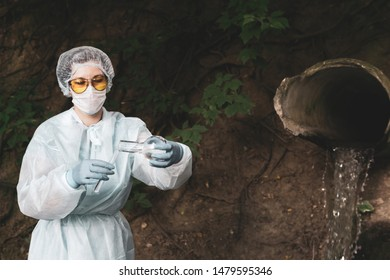 female biochemist or infectious disease specialist using test tubes conducts a chemical test of water against the background of a pipe with leaking water
