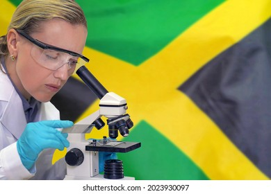 Female biochemist mixing substances to study under the microscope against Jamaica flag background. Medical technology and pharmaceutical research and development of science concept in Jamaica