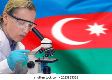 Female biochemist mixing substances to study under the microscope against Azerbaijan flag background. Medical technology and pharmaceutical research and development of science concept in Azerbaijan