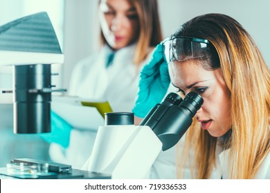 Female biotechnology scientists working in laboratory