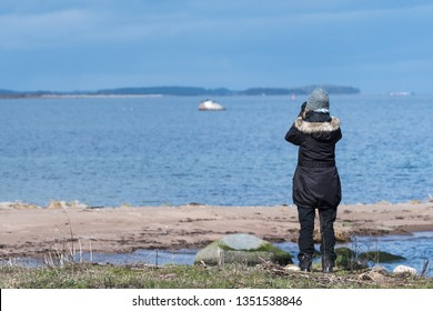 Female bird watcher by the coast in early springtime on the island Oland in Sweden