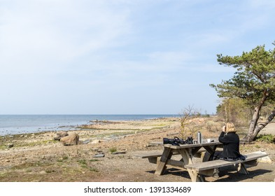 Female bird watcher takes a break by a wooden table at the swedish island Oland