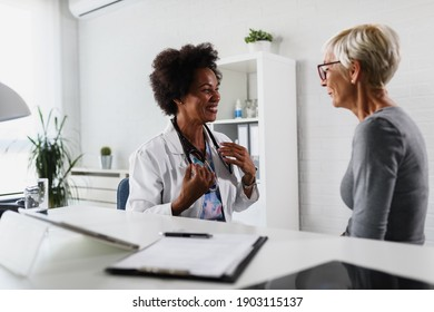 A female black ethnicity doctor sits at her office and examining elderly female patient
