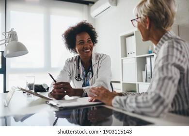 Eine schwarzweibliche Ethnizitätsärztin sitzt in ihrem Büro und spricht mit älteren weiblichen Patienten